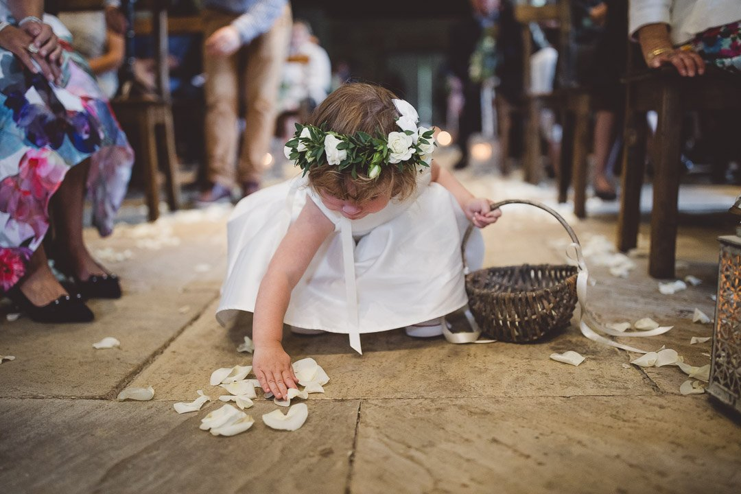 Flower girl collecting confetti from the floor