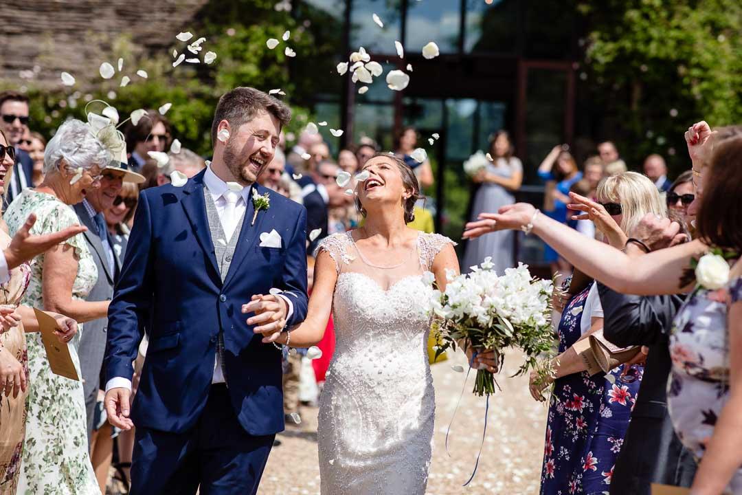 happy bride and groom under confetti